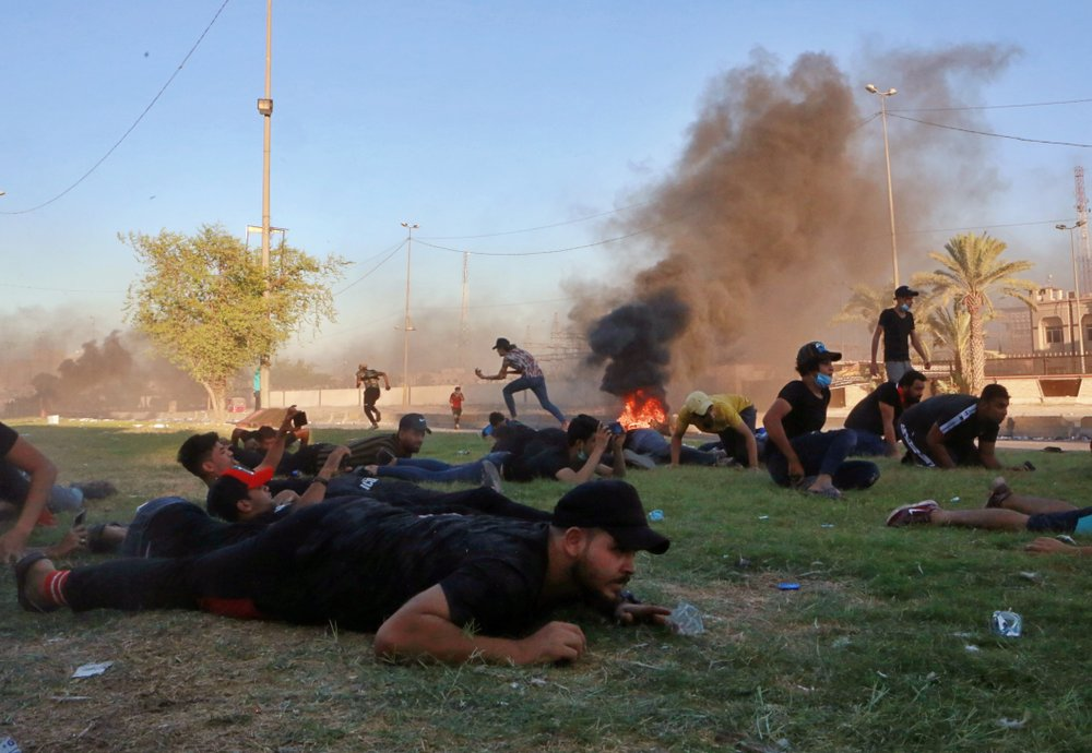 Anti-government protesters take cover while Iraq security forces fire during a demonstration in Baghdad, Iraq, Friday, Oct. 4, 2019.