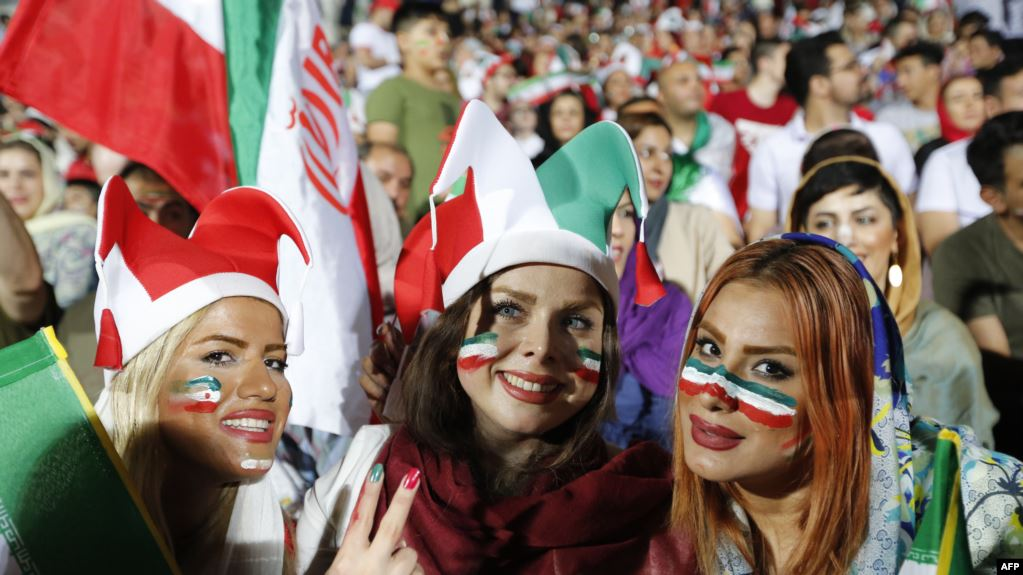 Iranian women cheer as they wave their country's flag after authorities in a rare move allowed a select female group into Tehran's Azadi Stadium to watch a friendly soccer match between Iran and Bolivia in 2018.