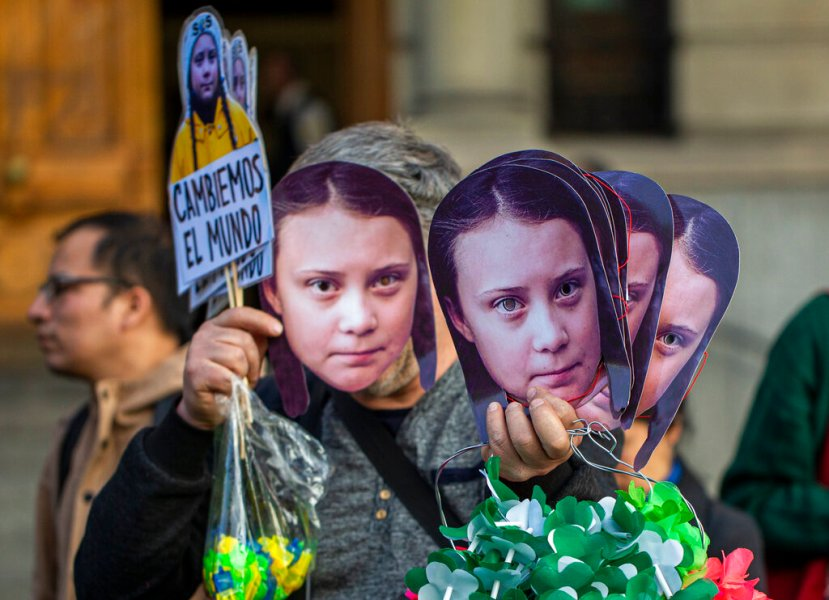 A man sells Greta Thunberg masks during a climate protest rally in Santiago, Chile, Friday, Sept. 27, 2019.