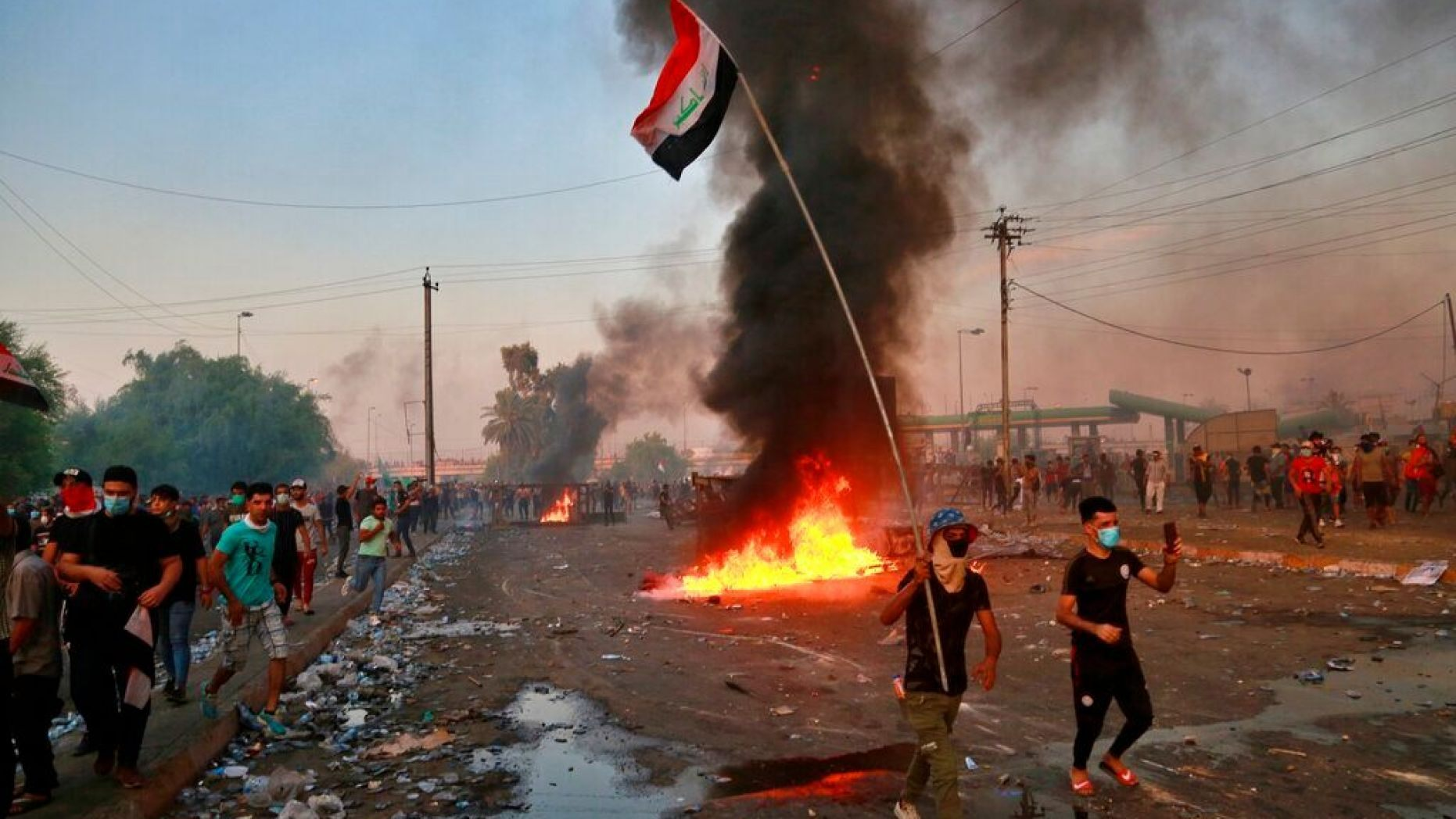 Anti-government protesters set fires and close a street during a demonstration in Baghdad, Iraq, Thursday, Oct. 3, 2019.