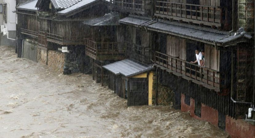 People watch the Isuzu River swollen by Typhoon Hagibis, in Ise, central Japan Saturday, Oct. 12, 2019.