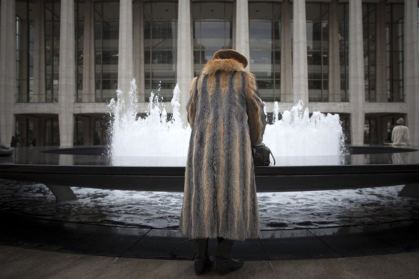 FILE PHOTO: A woman in a fur jacket goes through her handbag by the Lincoln Center's Revson Fountain during New York Fashion Week February 12, 2013.