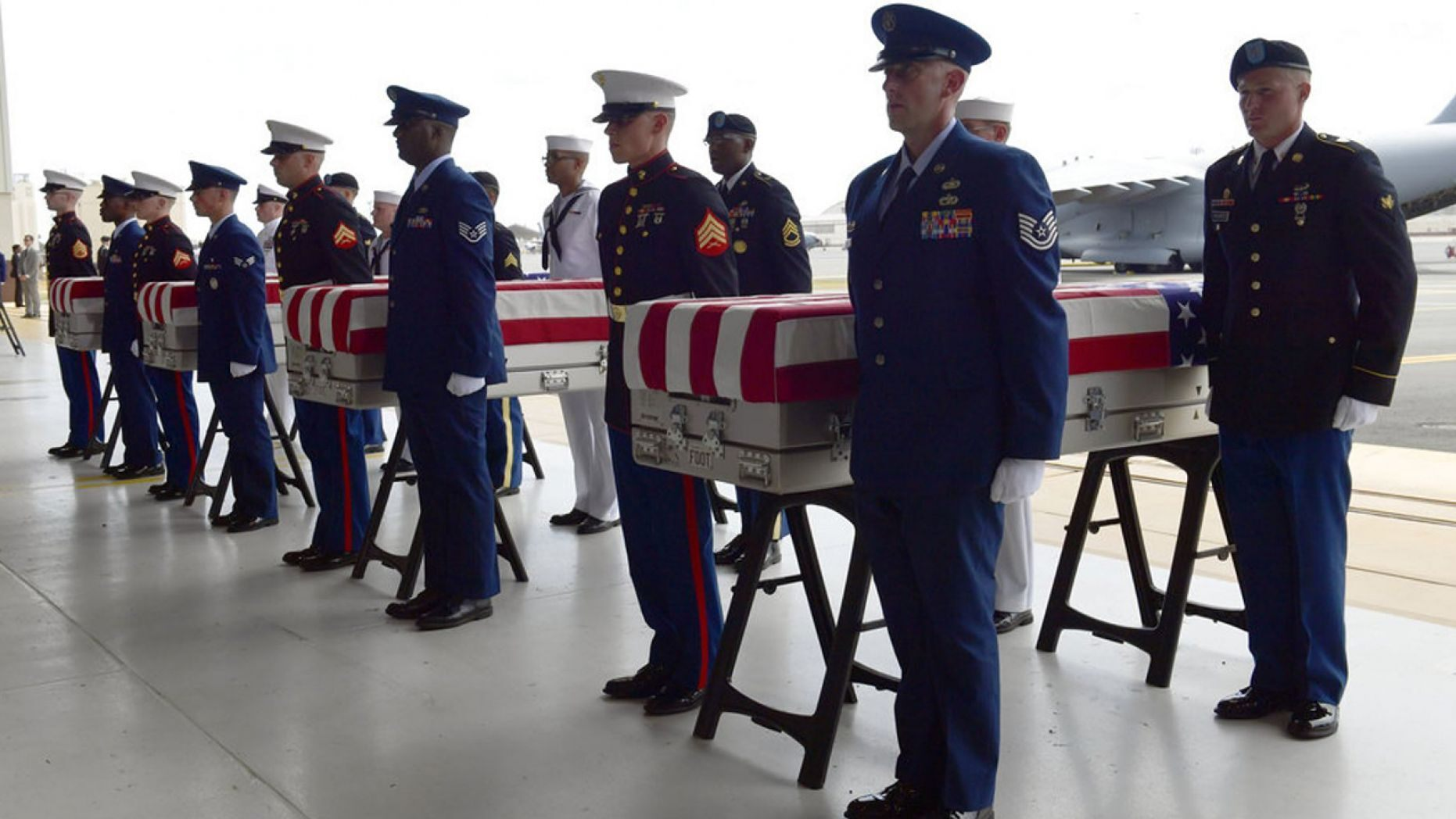Military members stand at attention after placing transfer cases in a hanger at a ceremony marking the arrival of the remains believed to be of American service members who fell in the Korean War at Joint Base Pearl Harbor-Hickam in Hawaii, in August 2018.