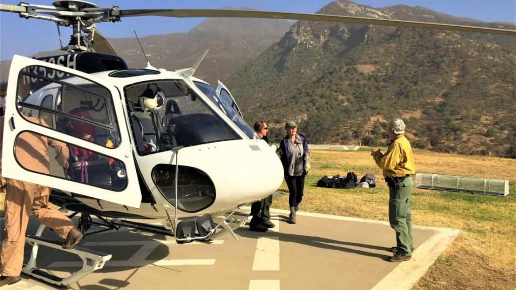 """Mrs. Gomez and Helitack team land at Helibase. """"S.O.S"""" spelled out with rocks saved a woman missing in a national park for days"""