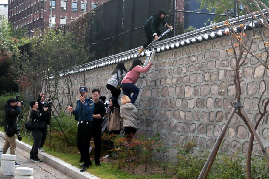 South Korean university students climb over a wall during a protest against the Special Measures Agreement, at Habib House, the U.S. ambassador's residence, in Seoul on Friday.
