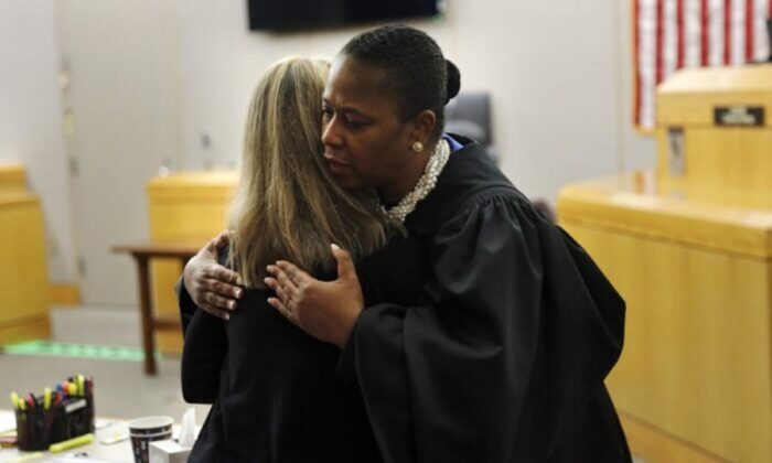 State District Judge Tammy Kemp gives former Dallas Police Officer Amber Guyger a hug before Guyger leaves for jail in Dallas on Oct. 2, 2019.
