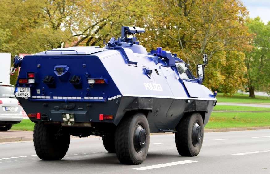 A police tank patrols at a crime scene near a Synagogue.