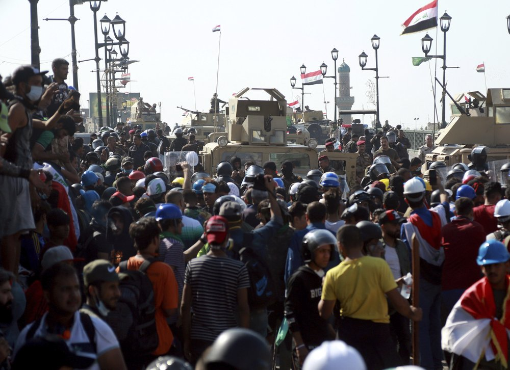 Iraqi Army soldiers try to prevent anti-government protesters from crossing the al- Shuhada (Martyrs) bridge in central Baghdad, Iraq, Wednesday, Nov. 6, 2019. Tens of thousands of people have taken to the streets in recent weeks in the capital, Baghdad, and across the Shiite south, demanding sweeping political change.
