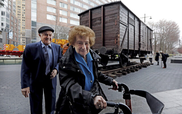 Holocaust survivors Leon Kaner, age 94, and his wife Ray Kaner, age 92, pass a vintage German train car, like those used to transport people to Auschwitz and other death camps, outside the Museum of Jewish Heritage, in New York, March 31, 2019.