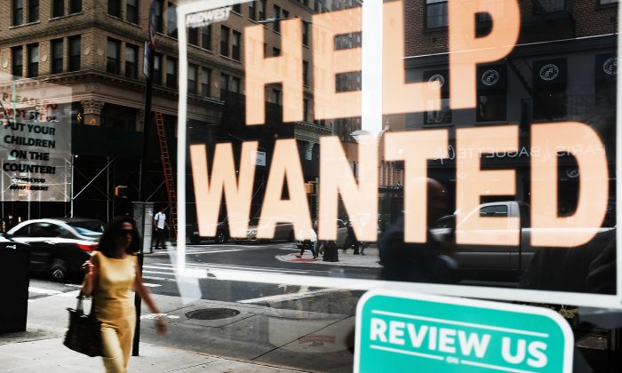 A help wanted sign is displayed in the window of a Brooklyn business in New York on Oct. 5, 2018.