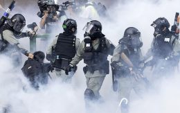 Police in riot gear move through a cloud of smoke as they detain a protester at the Hong Kong Polytechnic University in Hong Kong, on Monday.