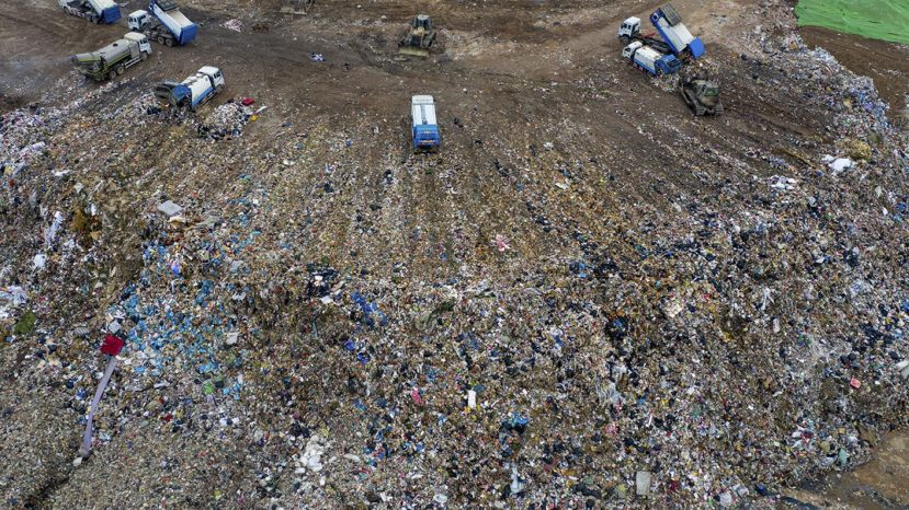 Chinese workers sort out and bury kitchen waste at the Jiangcungou Landfill, which is the China's largest refuse landfill, in Xi'an city, northwest China's Shaanxi province, 21 August 2019.