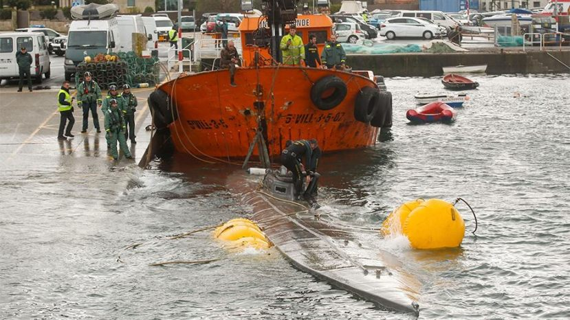 Spanish civil guard tow a sunken submarine believed to be carrying tons of cocaine in Aldan harbor, northwest Spain, on Tuesday.