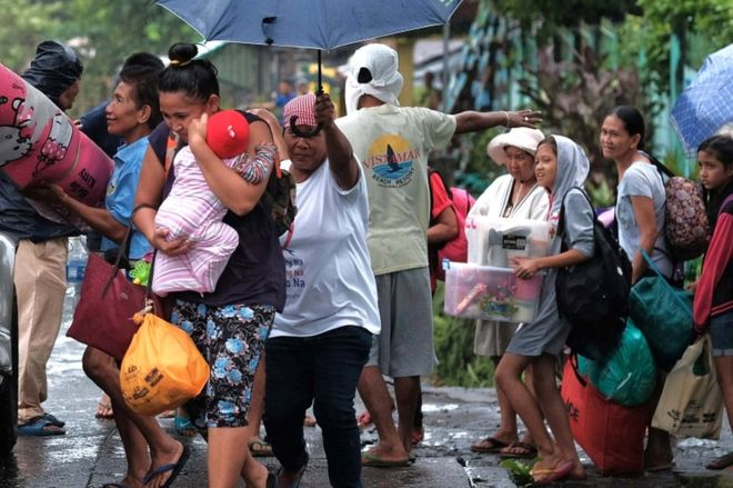 Villagers carry their belongings as they are evacuated in the eastern Philippines.