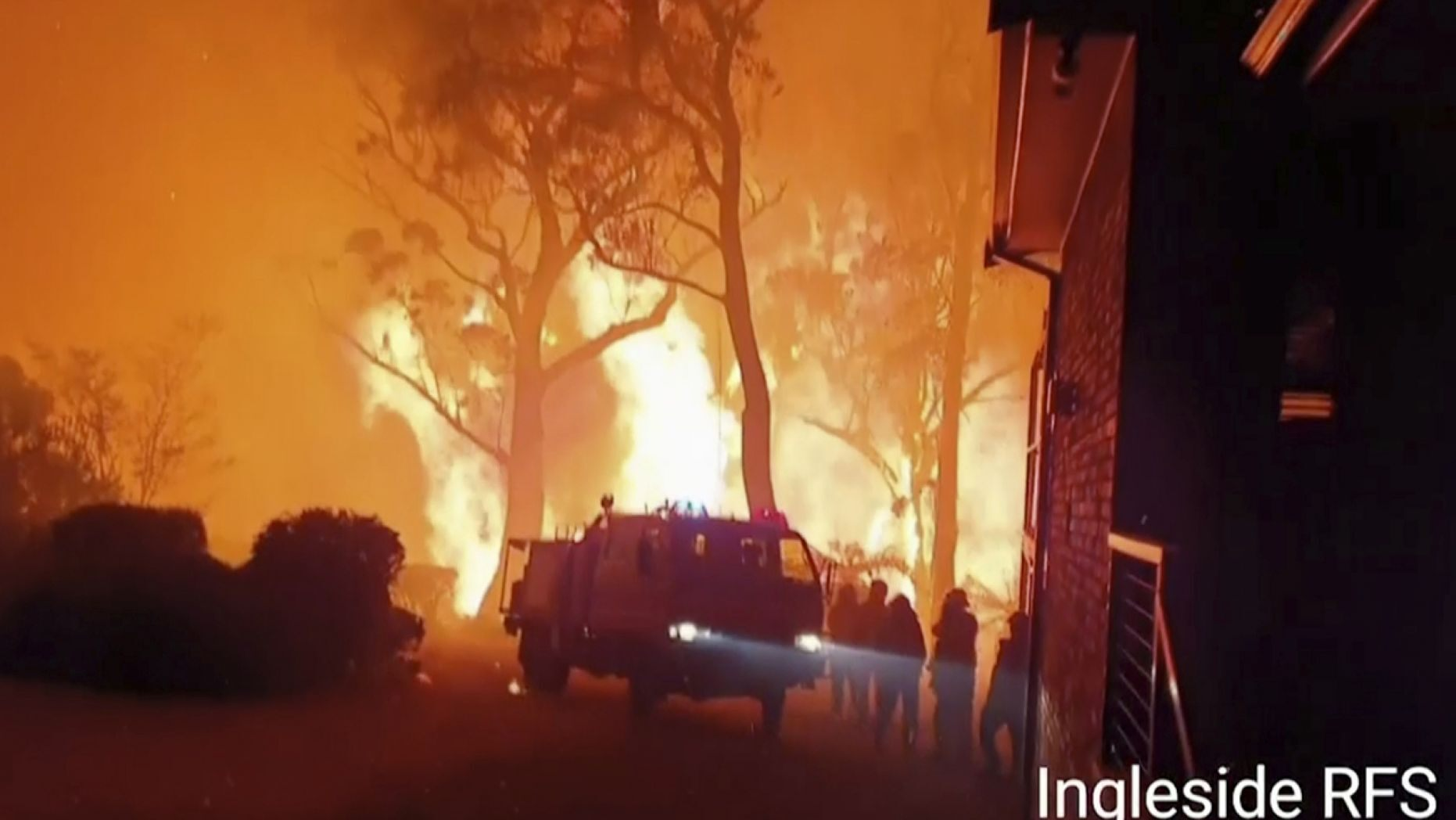 This image made from video taken on Dec. 22, 2019, and provided Dec. 25, 2019, by Ingleside Rural Fire Brigade, shows the wildfire behind an emergency vehicle near property on Hat Hill Road in Blackheath, New South Wales.