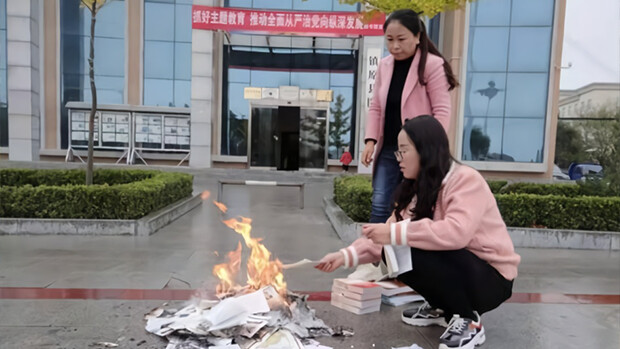 Two workers are seen burning books in front of the Zhenyuan county library in Qingyang City, Gansu Province, on Oct. 22, 2019.