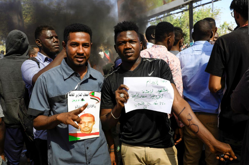 Sudanese civilians gather outside the court during the sentencing of 27 members of the national intelligence service to death by hanging over the killing of a teacher in detention in February during protests that led to the overthrow of former president Omar al-Bashir, in Omdurman, Sudan December 30, 2019.