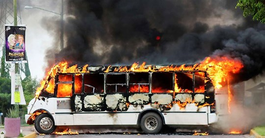 "A burning bus, set alight by cartel gunmen to block a road, is pictured during clashes with federal forces following the detention of Ovidio Guzman, son of drug kingpin Joaquin ""El Chapo"" Guzman, in Culiacan, Sinaloa state,"