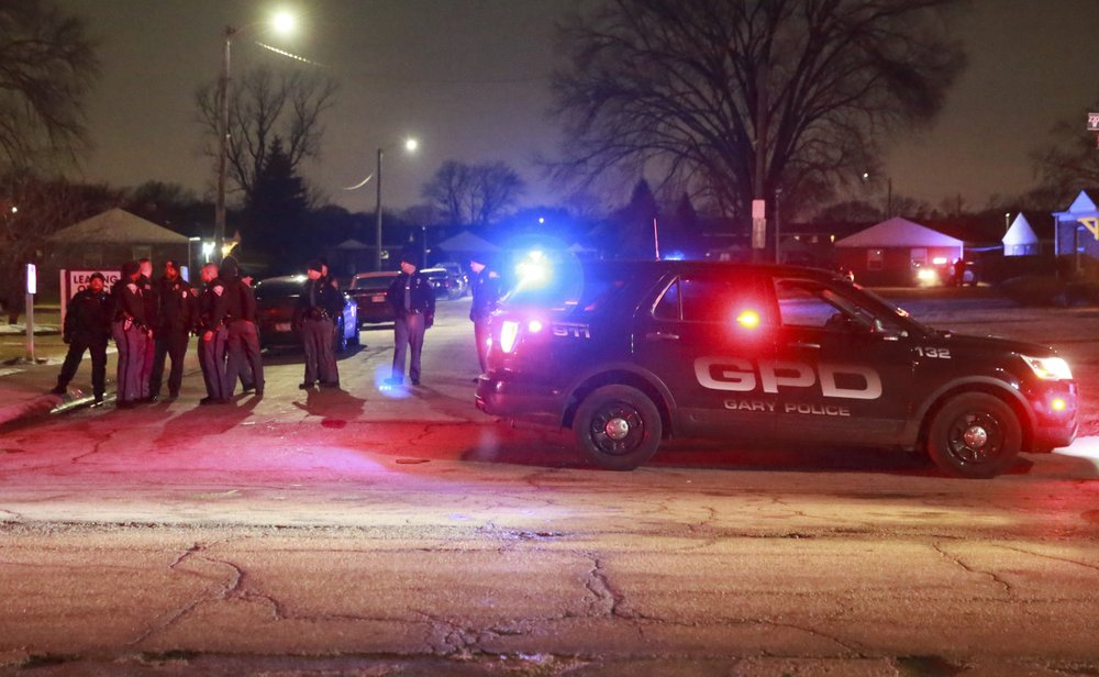 Gary and Indiana State Police officer stand at the entrance to the Westbrook Apartments where Gary police officers were wounded in a shooting incident Monday evening, Jan. 13, 2020 in Gary, Ind. One of the officers returned fire killing the suspect.