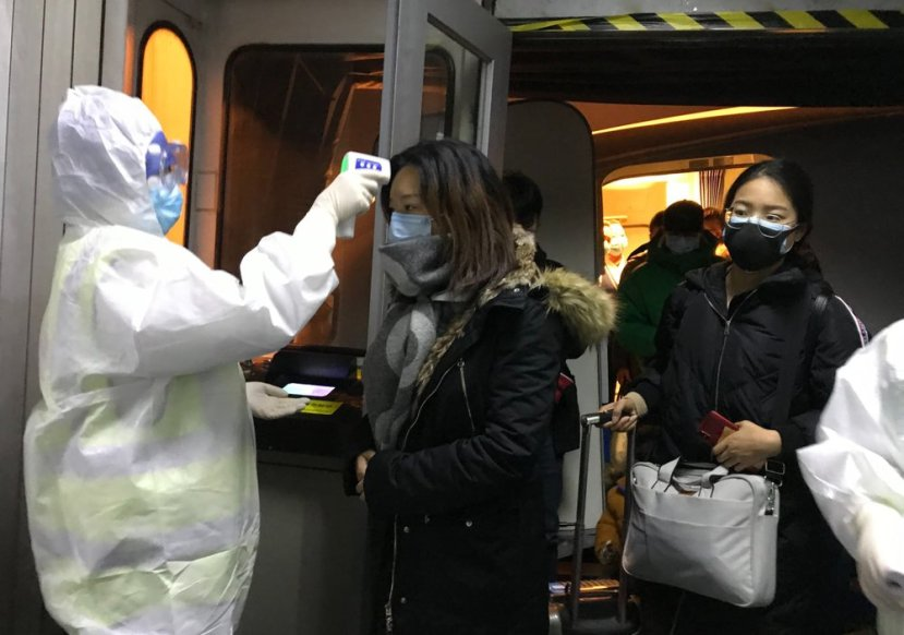 Health Officials in hazmat suits check body temperatures of passengers arriving from the city of Wuhan Wednesday, Jan. 22, 2020, at the airport in Beijing, China. Nearly two decades after the disastrously-handled SARS epidemic, China's more-open response to a new virus signals its growing confidence and a greater awareness of the pitfalls of censorship, even while the government is as authoritarian as ever.