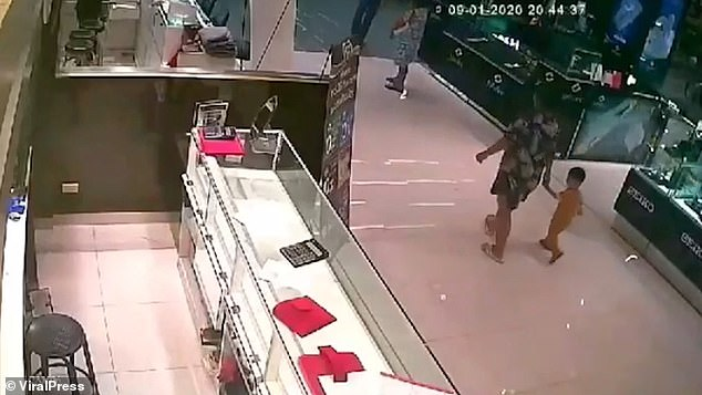A mother is seen on CCTV holding her two-year-old daughter's hand moments before the crazed gunman opens fire and kills the little girl, a security guard and a young woman.