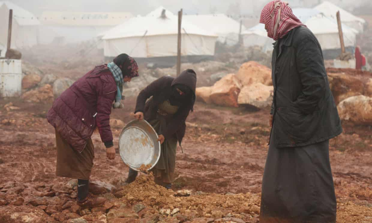 Displaced Syrians clear an area to set up tents after fleeing violence in Maarat al-Numan earlier this month. Photograph: Yahya Nemah/EPA
