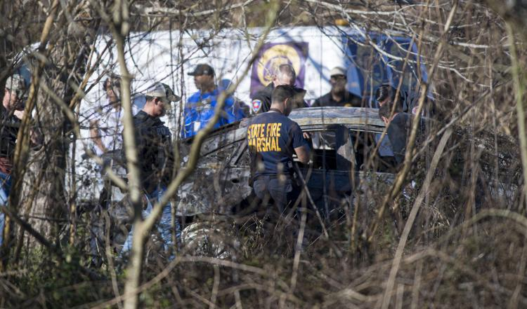 New Orleans police and fire marshal officials investigate the scene where a body was found in an abandoned burning car near Jourdan Avenue and N. Rocheblave Street in the Lower 9th Ward on Monday, January 6, 2020.