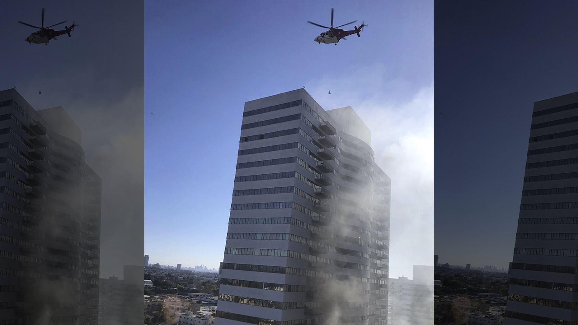 A helicopter flies over a residential building that is on fire in Los Angeles, Wednesday, Jan. 29,