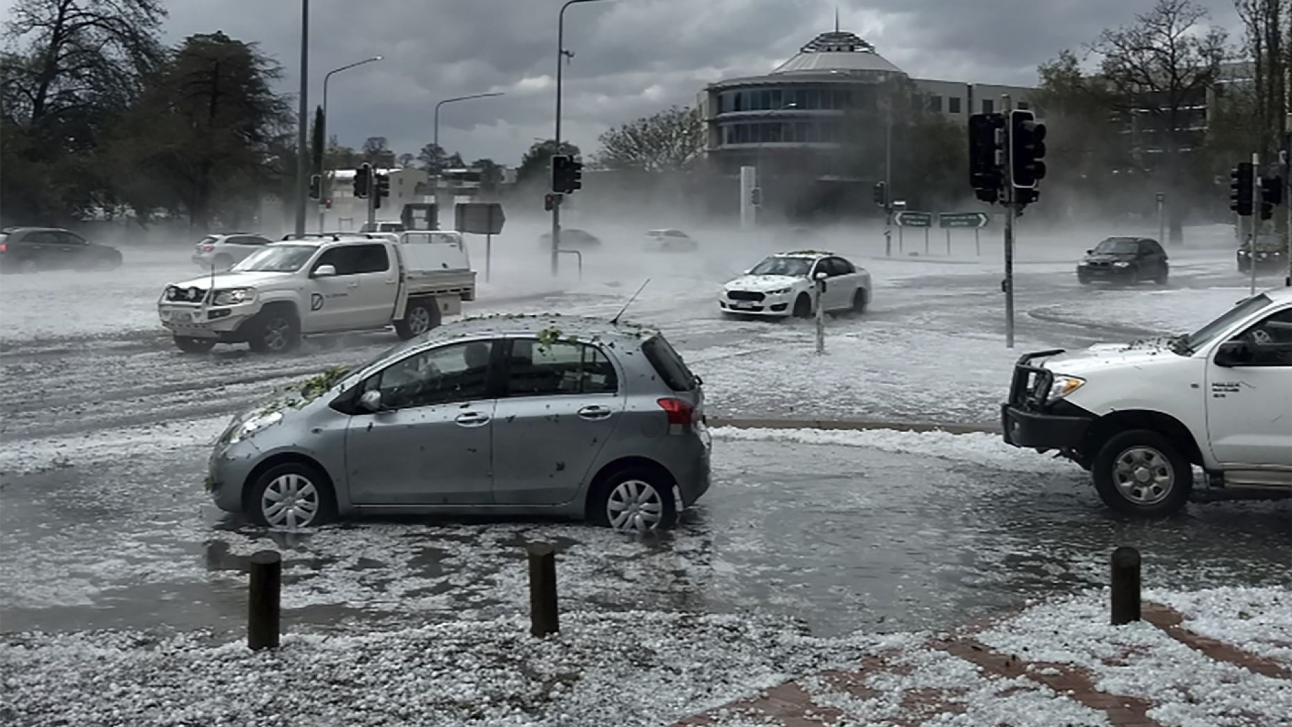 Hail covers vehicles in an intersection Monday, Jan. 20, 2020, in Canberra, Australia.