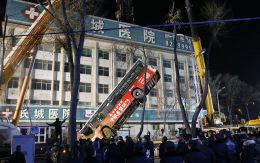 Rescue workers used a crane to raise the bus out from the hole so they could look for victims.