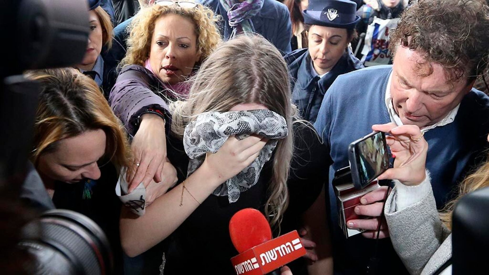 A 19-year-old British woman, center, who was found guilty of making up claims she was raped by up to 12 Israelis arrives at Famagusta District Court for sentencing on Tuesday, Jan. 7, 2020. She insisted she was raped and was coerced by investigators to retract her claim.