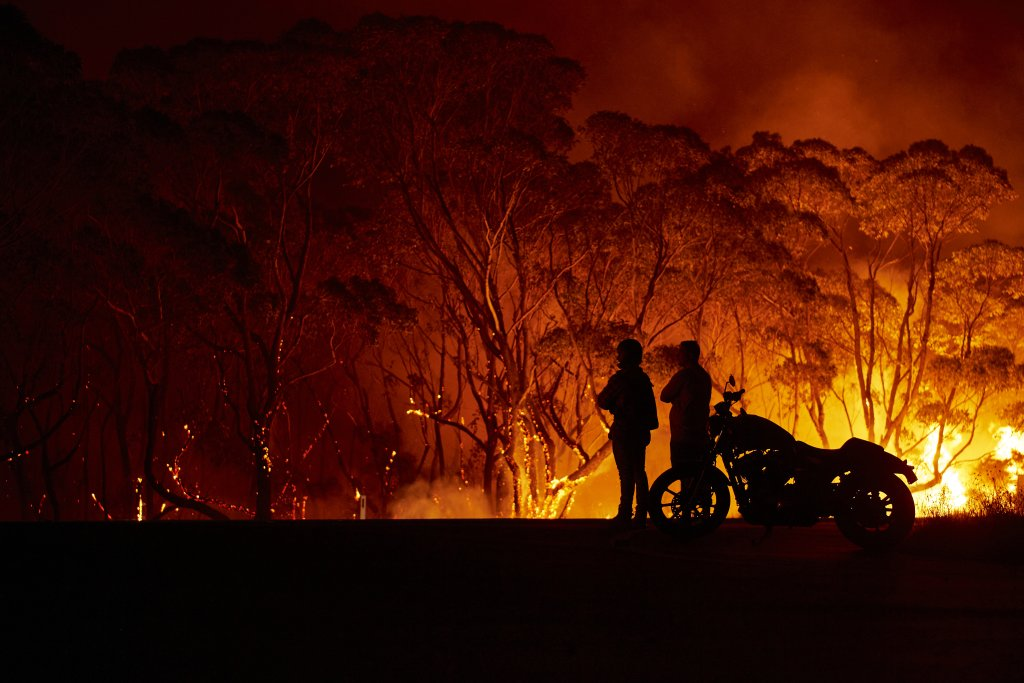 LAKE TABOURIE, AUSTRALIA - JANUARY 04: Residents look on as flames burn through bush on January 04, 2020 in Lake Tabourie, Australia.