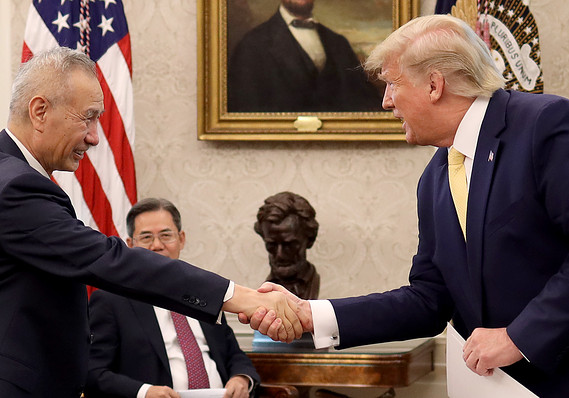 """U.S. President Donald Trump shakes hands with Chinese Vice Premier Liu He after announcing a """"phase one"""" trade agreement with China in the Oval Office at the White House October 11, 2019 in Washington, DC."""