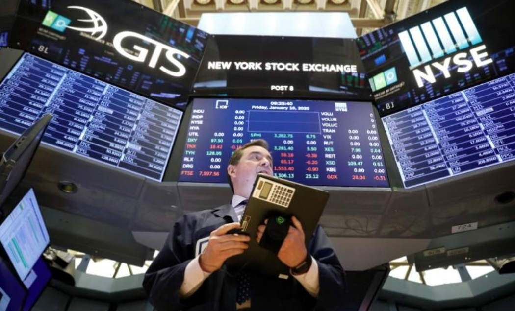FILE PHOTO: Traders work on the floor at the New York Stock Exchange (NYSE) in New York, U.S., January 10, 2020.