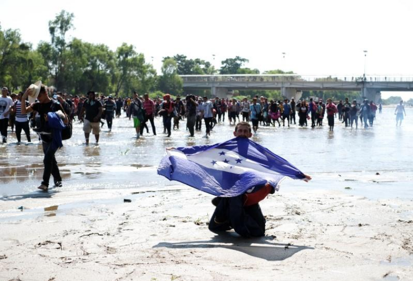 A migrant, part of a caravan travelling to the U.S., holds a Honduran flag as he cross the Suchiate river at the border between Guatemala and Mexico, in Ciudad Hidalgo, Mexico, January 20, 2020.
