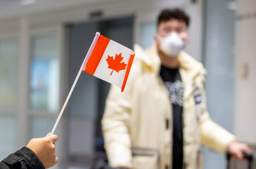 FILE PHOTO: A traveller wears a mask at Pearson airport arrivals, shortly after Toronto Public Health received notification of Canada's first presumptive confirmed case of novel coronavirus,