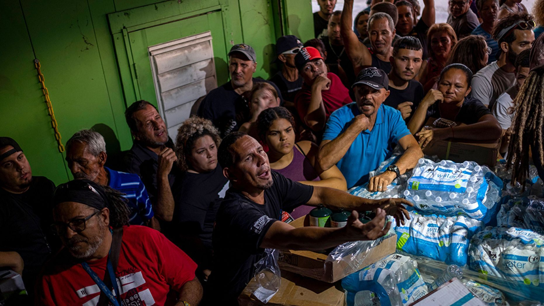 People break into a warehouse with supplies believed to have been from when Hurricane Maria struck the island in 2017 in Ponce, Puerto Rico on Jan. 18, 2020, after a powerful earthquake hit the island.