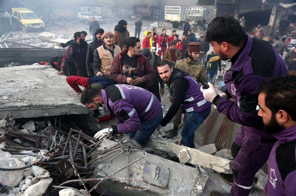 Rescuers search for survivors Wednesday under a collapsed building following an airstrike in Idlib province, Syria.