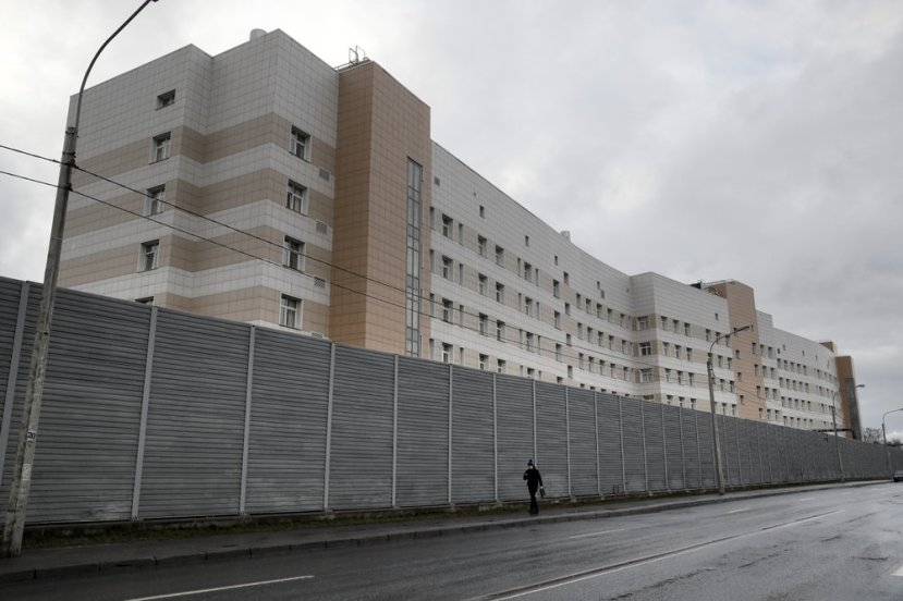 A man walks past a fence in front of the Botkin hospital in St. Petersburg, Russia, Wednesday, Feb. 12, 2020.
