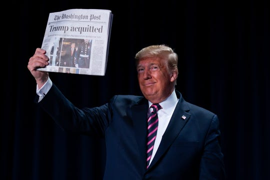 "President Donald Trump holds up a newspaper with the headline that reads ""Trump acquitted"""
