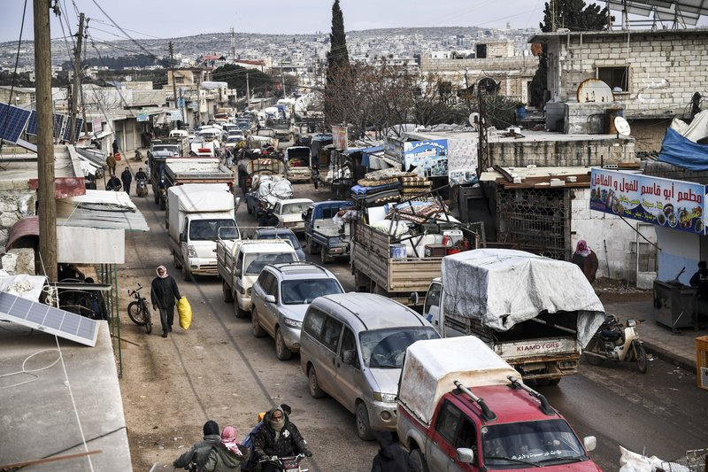 Civilians flee from Idlib toward the north to find safety inside Syria near the border with Turkey, Saturday, Feb. 15, 2020.