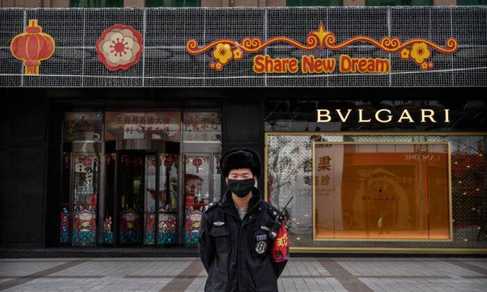 A Chinese security guard wears a protective mask as he stands on a commercial street in Beijing, China, on Feb. 18, 2020.