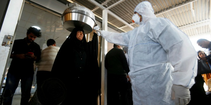 An Iraqi medical staff member checks a passenger's temperature, amid the new coronavirus outbreak,