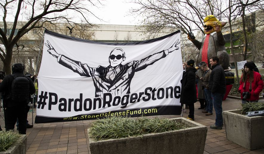 "Supporters of Roger Stone with a banner that reads ""#PardonRogerStone"" wait outside federal court in Washington, Thursday, Feb. 20, 2020."