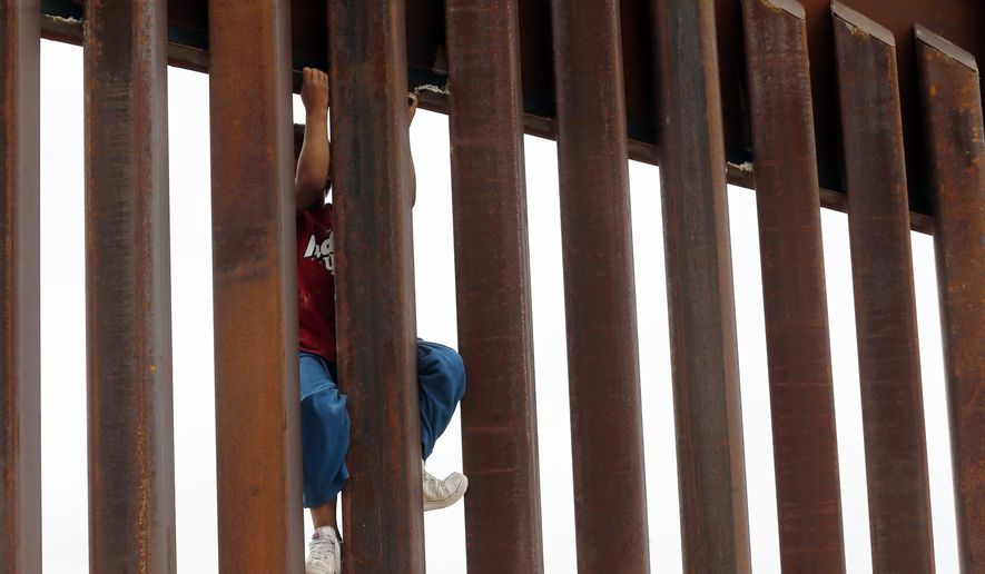 Children from Anapra, Mexico, climb a section of the new border wall recently built near Santa Teresa, N.M., Monday, April 9, 2018.
