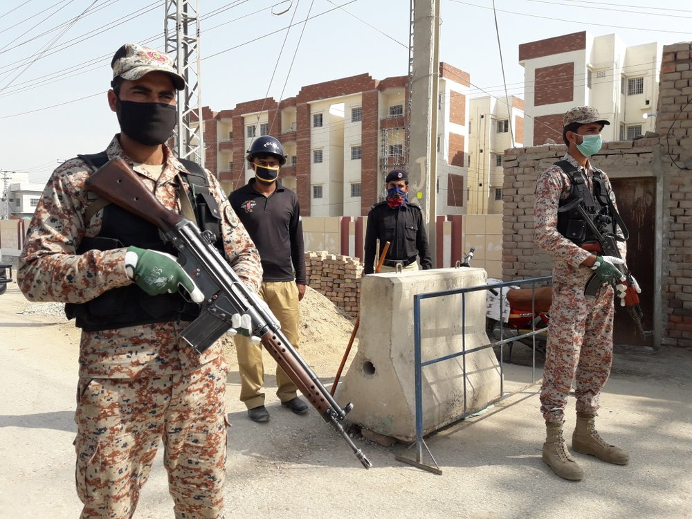Pakistani security personnel stand guard outside apartments that were converted to a quarantine facility for people suspected of being exposed to the coronavirus after having travelled to Iran, in Sukkar, Pakistan,