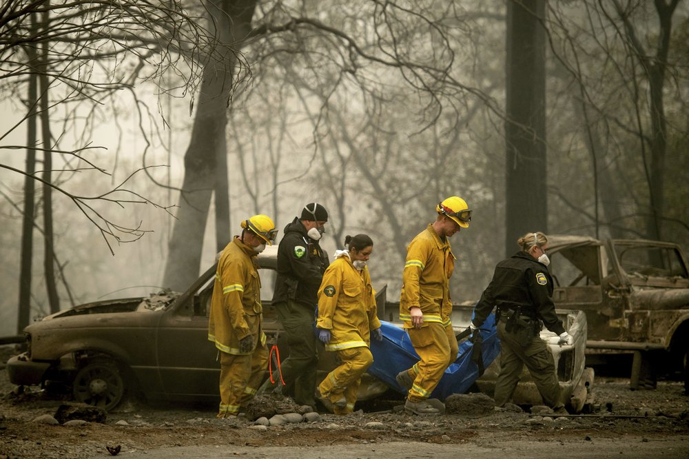 In this Nov. 14, 2018, file photo, firefighters and deputies carry the body of a Camp Fire victim at the Holly Hills Mobile Estates in Paradise, Calif.