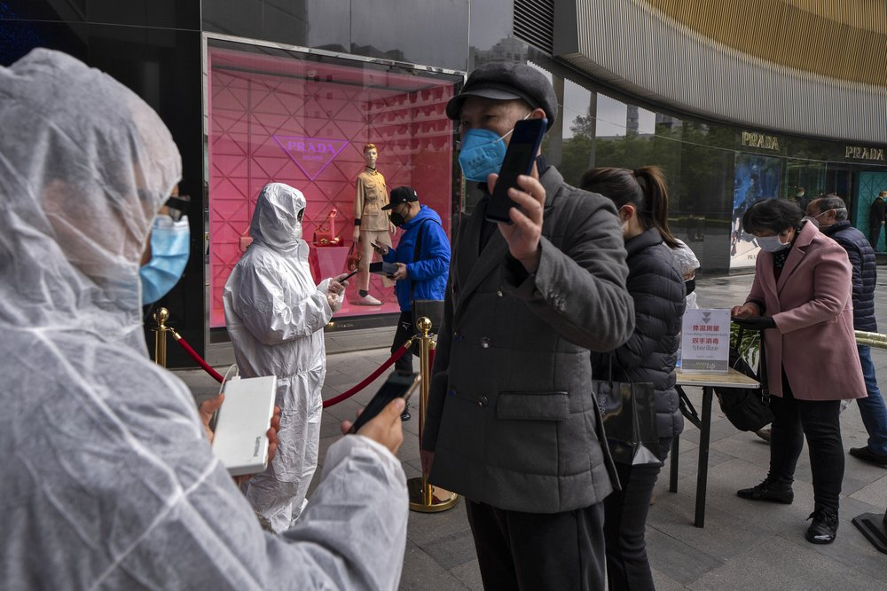 In this photo released by Xinhua News Agency, workers wearing protective suits check customers' health QR codes at the entrance of a re-opened shopping mall in in Wuhan in central China's Hubei province, Monday, March 30,