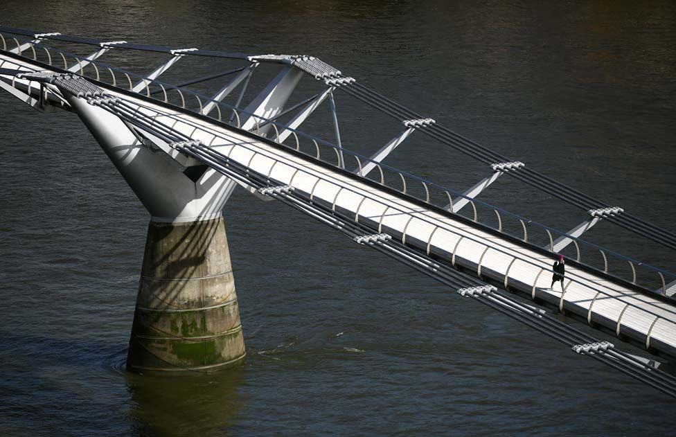 A woman walks across an empty Millennium Bridge during London's rush hour.