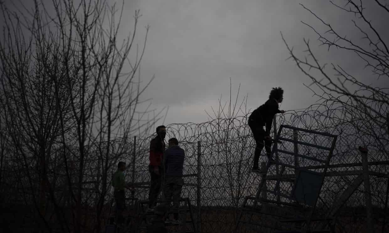 Migrants and refugees attempt to scale the border fence from Turkey into Greece. Photograph: Felipe Dana/AP